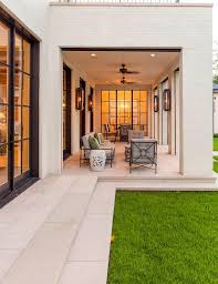 white wrought iron furniture. chic covered patio boasts wrought iron living and dining furniture illuminated by glass wall sconces facing steel framed windows looking into the white