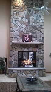 Aspen Dressed Fieldstone by Boral Cultured Stone with limestone hearth and  mantel.