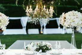 chandelier with flowers and greenery hangs over dinner table free photo
