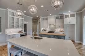 beautiful kitchen with sparkling white quartz counter island butcher block island and marble backsplash