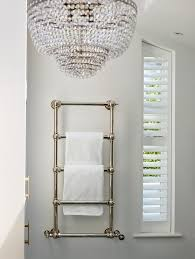 wall mounted towel warmer next to plantation shutters on angled window