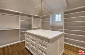 pure white closet with chandelier lighting and table cabinet