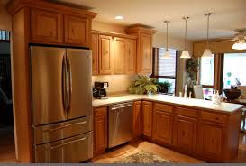 starmark cabinetry with modern refrigerator and pendant lighting for traditional kitchen design