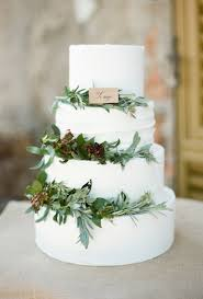 Four Tiered Wedding Cake Decorated With Greenery Brides