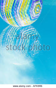 pool water with beach ball. Beach Ball Reflected In Swimming Pool Water - Stock Photo With