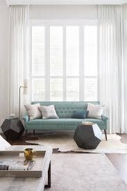 blue tufted settee sofa with white cowhide rug