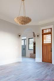 living room light gray walls grey gold chandelier black window sashes whitewashed hardwood flooring light blue doors 1 of 6