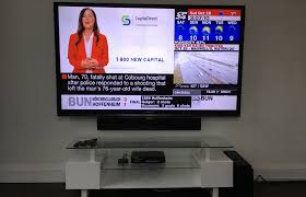 80 sharp tv mounted against drywall metal studs in condo with definitive technology sound bar mounted directly below the tv