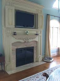 custom distressed white fireplace surround marble inlay around fireplace tv above fireplace tv cabinet above fireplace
