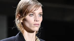 a white model with dirty blonde hair in a side part walks down the dries van