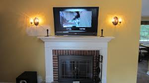 mounting tv above black and red brick fireplace with white mantel shelf plus two wall sconces on soft yellow painted wall