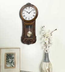 brown wooden pendulum wall clock by
