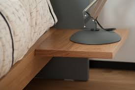 A close up of the bedside table attached to the headboard and frame of the  Koo
