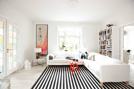 living room modern orange accents black and white striped rug white sectional sofa