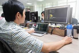 developer office. asian outsource software developer looking screen sitting at desk working laptop computer mobile application real office stock photo colourbox