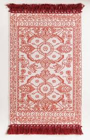 photo courtesy of food52 clear rug with traditional red fl pattern printed on it and red fringe