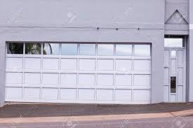 double garage door and pedestrian door cream grey reflective decor colors road entrance stock photo