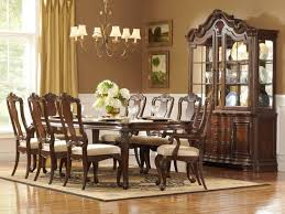 traditional formal dining room with 9 pieces dining sets with carved dark wooden chairs and table with beige cushion and also simple vintage chandelier