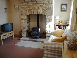 i love the idea of a wood stove inside the fire place stone hearth