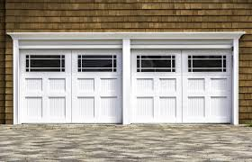 natural wood shingle siding surrounds this two car garage in white painted wood featuring large
