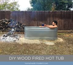 this diy wood fired hot tub is made from a stock tank and copper tubing and