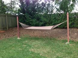 easy diy project for our hammock posts 8 ft tall each into the ground with cement then just 2 hooks and that s it a hammock with spreader bars