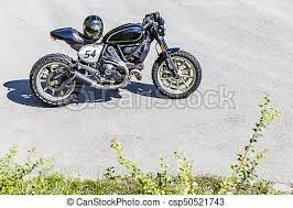 custom made scrambler style cafe racer with helmet standing on road csp50521743