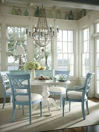 round dining room furniture with round white dining table and light blue dining chairs on beige rug and dark wood floor with gl bottles o