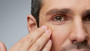 man rubbing clear cream under his eyes