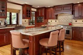 this kitchen with cherry wood cabinetry coordinates nicely with the reds in the granite worktop