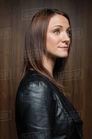 pensive brunette woman wearing leather jacket looking away