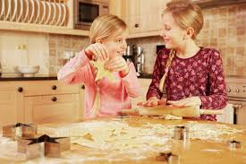Two Girls Baking Star Shape Pastry At Kitchen Table Stock Photo