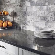 a freckled charcoal gray quartz countertop paired with an ont gray marble mosaic tile