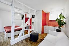 Surprisingly Small Apartment in Paris with a Charming Red and White Interior  Shop this look: ottoman, couch, comforter.