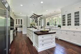 luxury white kitchen with marble island hanging pots and pans and hardwood flooring