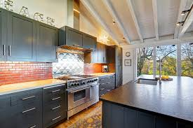 the black matte cabinetatte finish of the kitchen island countertop complement the wooden vaulted