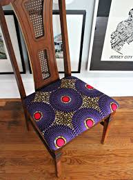 the royal chair wooden chair upholstered with a purple african fabric with some pink highlights