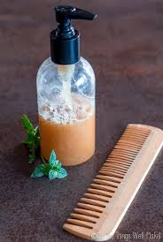 a homemade peppermint clarifying shampoo in a pump bottle next to peppermint sprigs and a wooden