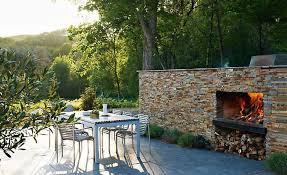 outdoor stone veneer fireplace with norstone ochre blend stacked stone rock panels in a garden