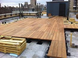 a pedestal decking system being installed on a rooftop in manhattan