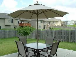 decorating small outdoor patio with umbrella design ideas using small square dining table and 4 chairs