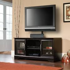 black varnished teak wood tv stand with mount for middle size screen tv using clear glass door