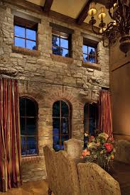 dining room with rustic stone accent wall and brick window cills