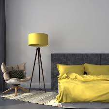 yellow tiffany style floor lamps near small cream chair and small bedding with two yellow pillows also small rug in minimalist bedroom design