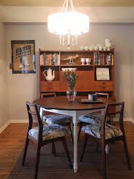 modern round dining room table. Delightful Chandelier Above Minimalist Round Table And Chair Beside Bookshelve. Elegant Design Of Modern Dining Room