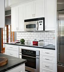 two toned black and white kitchen features an induction cooktop fixed to a honed black marble countertop above a stainless steel oven fixed between white