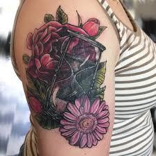красивая татуировка песочных часов со цветами на плече девушки