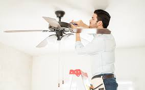 a man on a ladder adjusting ceiling fan housing with a driver