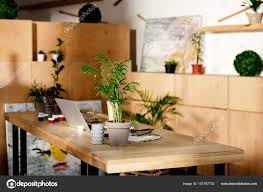 interior artist studio painting supplies laptop potted plants wooden table stock photo