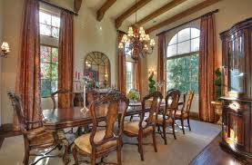 ornate dining room table and chairs. exposed wood beams above ornate dining set. chair seats are plush velvet. twin topiaries room table and chairs a
